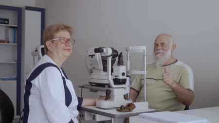 phoropter : Phthalmologist and elderly look at camera, man show thumb up