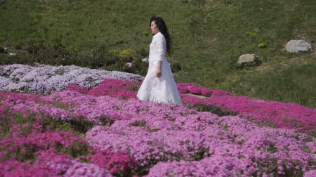 obcasy : Charming brunette walks among pink flowerbeds in botanical garden