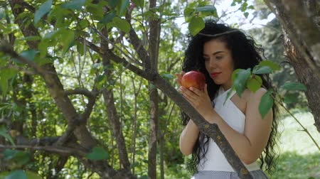 poisoned : Beautiful brunette with red apple stand near the tree