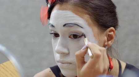 contornos : Girl mime draw black lines on her eyelids in front of the mirror Vídeos