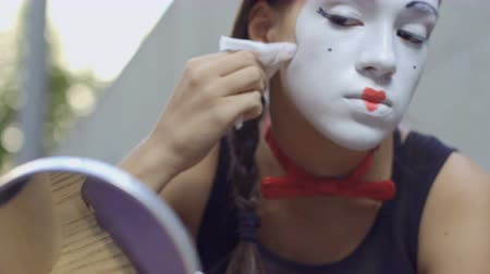 contornos : Young girl mime correct white mask on her face with wet napkin
