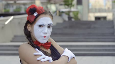 greasepaint : Cute girl mime crosses hands on her chest and suspiciously looking at the camera Stock Footage