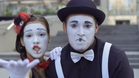 greasepaint : Young man and woman mimes gesticulating hands on camera Stock Footage