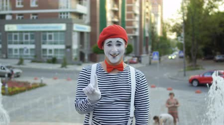 greasepaint : Funny mime in red beret show thumb up at fountain background