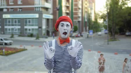 okey : Mime in red beret and stripped shirt show two signs okey on camera Stock Footage