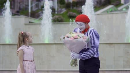 давать : Cute mime in red beret give bouquet of flowers to a little girl Стоковые видеозаписи