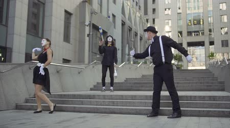 gesticulation : Three mimes at office center background