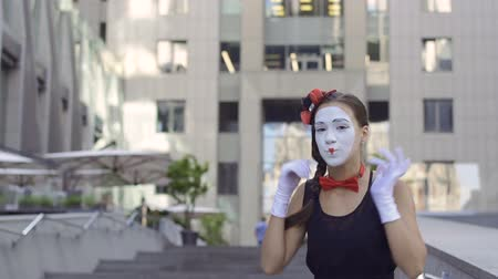 fool : Pretty mime girl playing her role at office center background