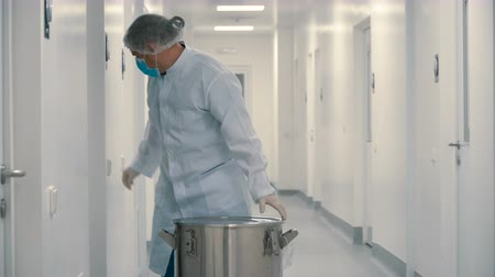 doorway : Chemist carries instruments in metallic barrel for sterilization