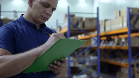 auditor : Inspector check the packages in warehouse and writing report Stock Footage