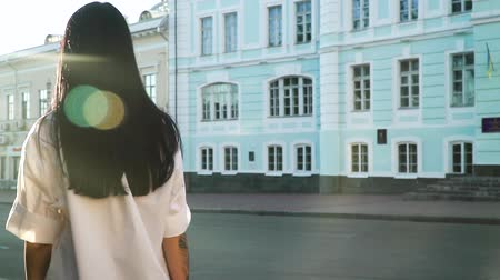 mavi arka : Long-haired brunette in white shirt is moving forward from camera in slow motion