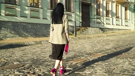 sandals : Confident and stylish brunette walking at stone road in the city in slow motion