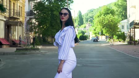 handbag : Elegant brunette in white skirt, stripped tunic and sunglasses walk in the city