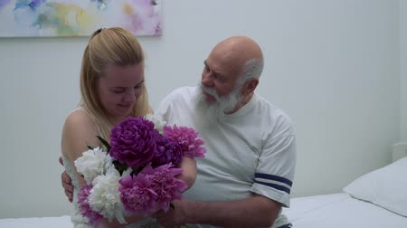 piwonia : Young girl bring bouquet of flowers to his grandfather in hospital Wideo
