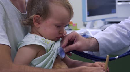médicos : Pediatrician listening the breathing of little girl with stethoscope