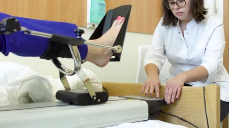 recovering : Doctor control the leg of patient during procedure of mechanotherapy