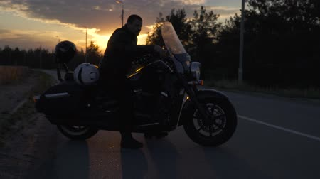 ajustando : Biker sitting on motorcycle at sunset background