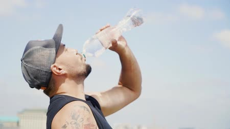 svetr : Guy in a cap and with a tattoo is drinking water