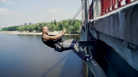 exhilaration : Guy at the edge of the bridge checks the insurance