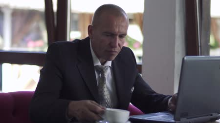 technics : Businessman drinks coffee sitting at table in restaurant and working at laptop