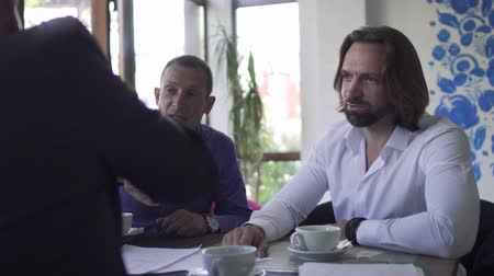 shake hair : Three businessmen make a successful deal at restaurant Stock Footage