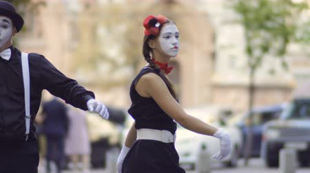 gesticulation : Man and woman mimes dancing at blurred urban street