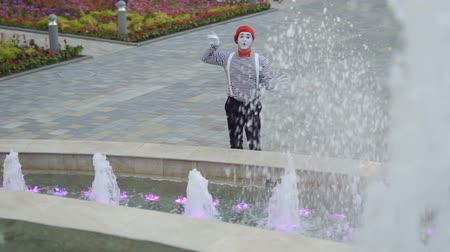 greasepaint : Funny mime touching invisible wall standing near fountains