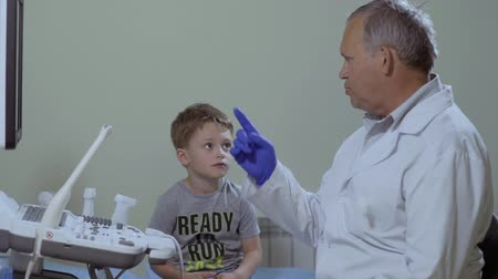 cardiologista : Doctor talk with little boy in the cabinet near medical ultrasound Stock Footage