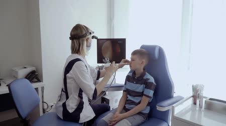 impaired : Doctor check nose of boy with ENT telescope