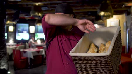 padeiro : Cook holds basket with fresh bread shoti and smiling to camera