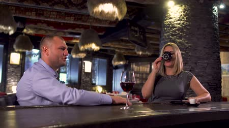embarrassed : Man and woman sitting near bar counter and drinking wine and coffee