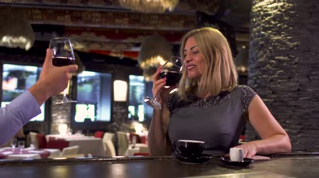 дружелюбный : Happy adult couple drinking wine sitting at bar counter in restaurant