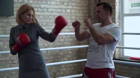 feminity : Woman in elegant dress, boxing gloves training at boxing ring with trainer