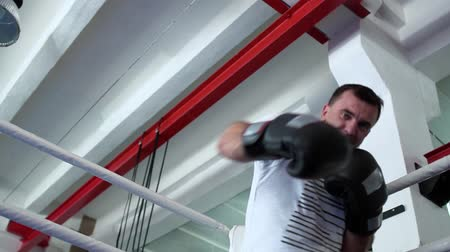 treinador : Boxer in boxing gloves hitting with invisible opponent at boxing ring and win