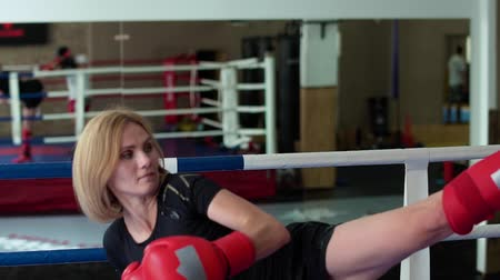 feminity : Beautiful woman in boxing gloves training her hits with coach at boxing ring Stock Footage