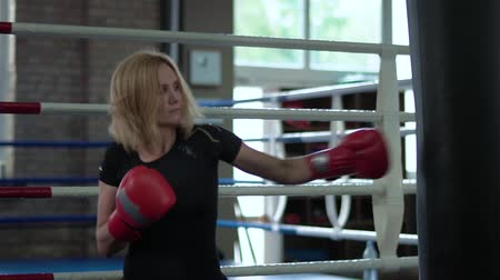 átlyukasztás : Pretty sports woman boxing with punchbag in the gym