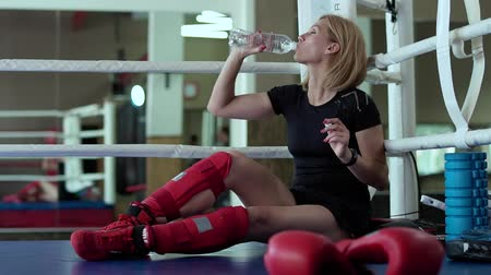 kimerültség : Tired woman sit at the corner of boxing ring and drink water