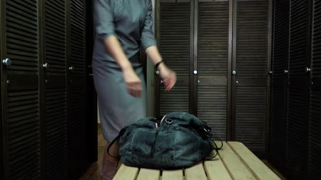 кроссовки : Businesswoman come to dressing room and take out boxing gloves from bag