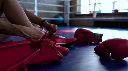 tornacipő : Sportswoman tie shoelaces before fighting at boxing ring