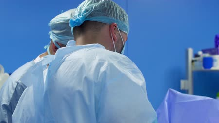 paramedics : Surgeons make operation in blue operating room