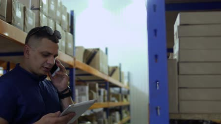 caixa de correio : Inspector talk by phone and checks the boxes on shelves in storage
