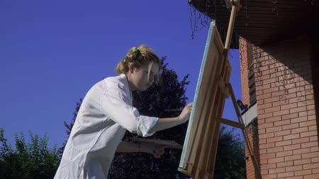resimlerinde : Young attractive girl paints on an easel Stok Video