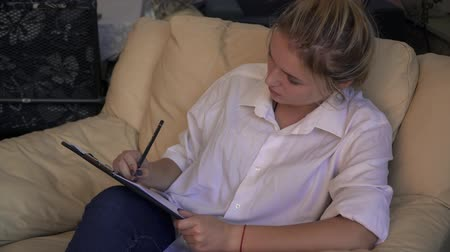armchairs : Charming young lady writes sitting in a leather armchair Stock Footage