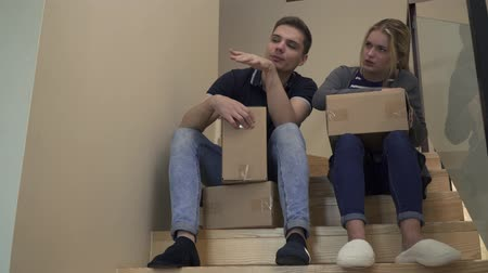 resimlerinde : Young attractive couple are sitting on the stairs in the house and talking
