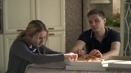 picture box : Young couple eating pizza in the kitchen