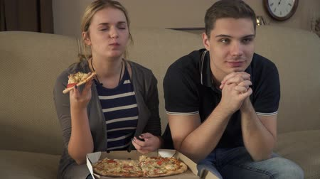 picture box : Young couple with a box of pizza sits on the couch