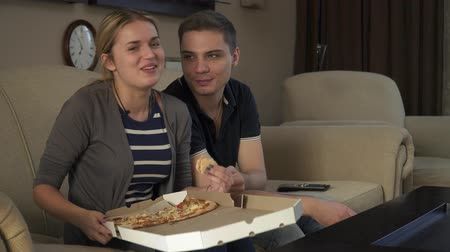 picture box : Beautiful young couple sitting on the couch and eating pizza