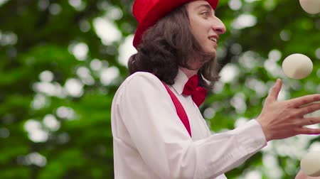 gesticulando : Young mime walks on stilts and juggling in the park