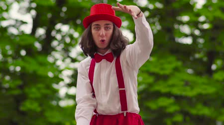 gesticulando : Funny young mime walks on stilts and juggling in the park