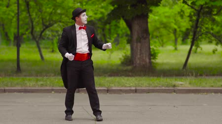 invisible : Mime shoots from invisible bow in the park Stock Footage